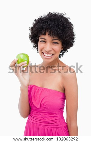 Young woman showing a great smile while holding a beautiful green apple - stock photo