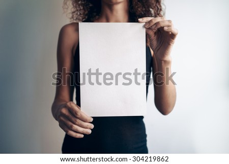 young woman showing a white blank page of clipboard - stock photo