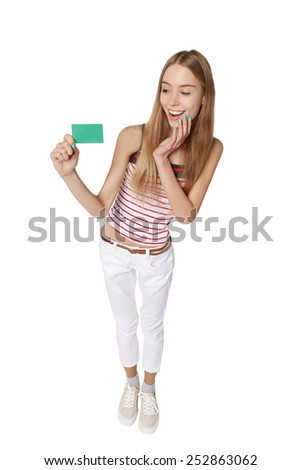 Young woman showing blank credit card. Happy smiling multi-ethnic female model isolated in full length on white background in high angle view - stock photo
