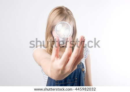 Young woman showing bright light bulb on the camera on the white background