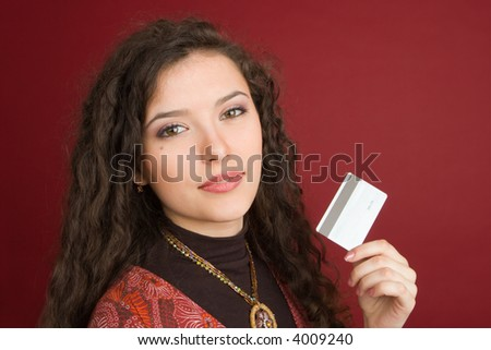 Young woman showing credit card isolated on red background - stock photo