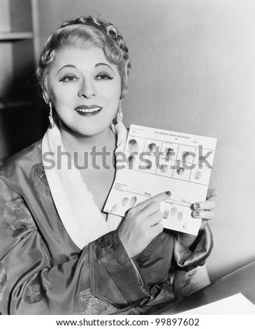 Young woman showing fingerprint on a sheet of paper - stock photo