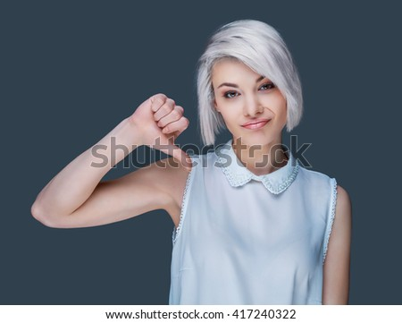 young woman showing her disliking of something with her thumb down, isolated against gray background - stock photo