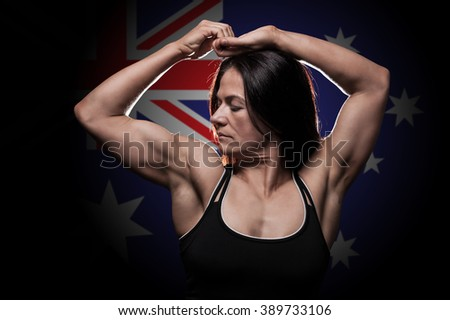 Young woman showing her muscles - with the Australian flag in the background - stock photo
