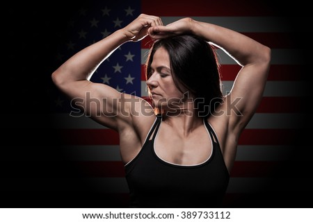 Young woman showing her muscles - with the USA flag in the background - stock photo
