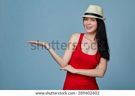 Young woman showing holding on the palm blank copy space over blue background - stock photo