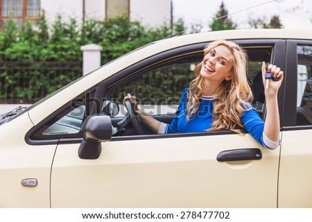 Young woman showing key in a car - stock photo