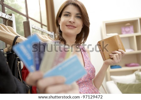 Young woman showing off her credit cards while standing in a fashion store.