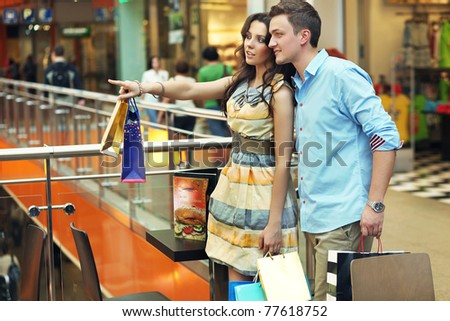 Young woman showing something at shopping center - stock photo