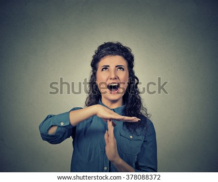 Young woman showing time out hand gesture, frustrated screaming to stop isolated on grey wall background. Too many things to do. Human emotions face expression feelings reaction - stock photo
