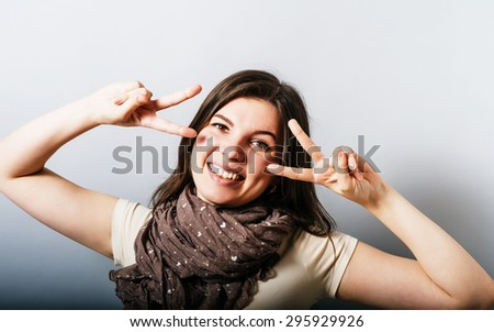 Young woman showing victory gesture, looking through her fingers. On a gray background.