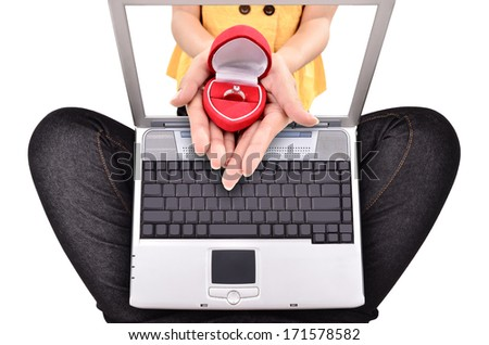 young woman shows a ring from the laptop, isolated on white background - stock photo