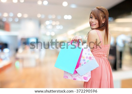 Young woman shows an ecstatic expression while holding shopping bags