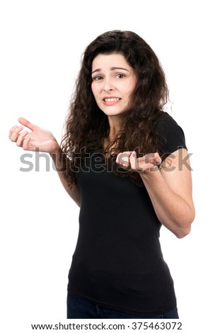 Young woman shrugs her shoulders showing her indecision and inability to make a decision. - stock photo