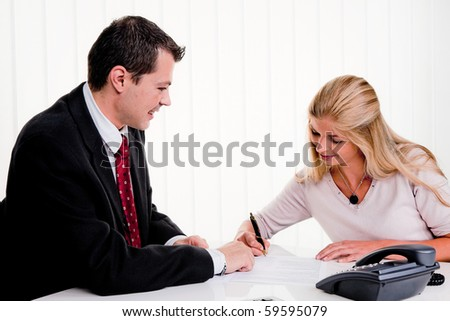 Young woman signs a contract in an office - stock photo