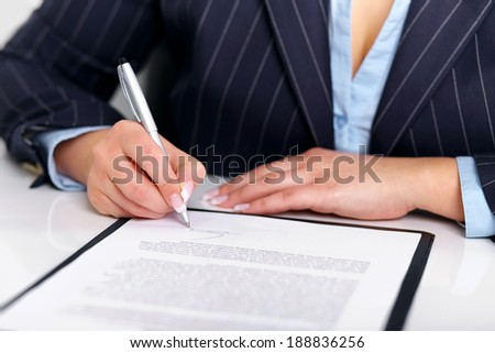 Young woman signs a contract on a white table - stock photo