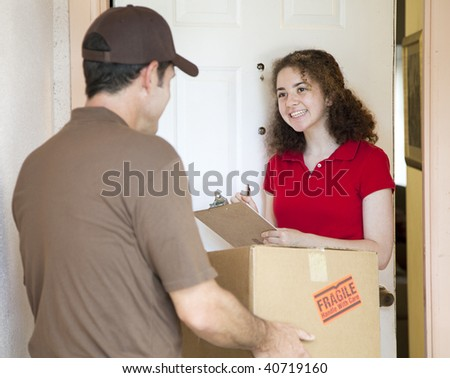 Young woman signs for a package delivered by a courier. - stock photo