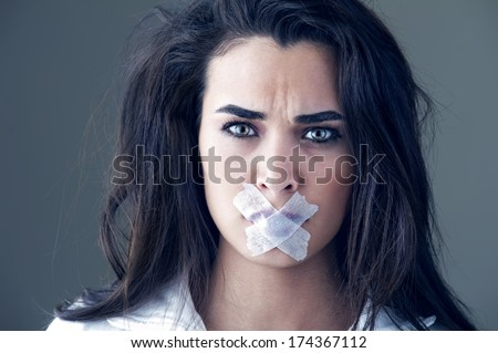 Young woman silenced with a masking tape - stock photo