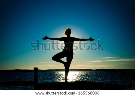 Young Woman Silhouette Ballet with open arms dancing to the sea on Summer Sunset - stock photo