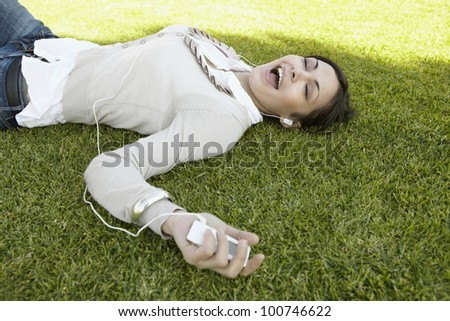 Young woman singing along to the music she's hearing with her headphones, laying down on green grass. - stock photo