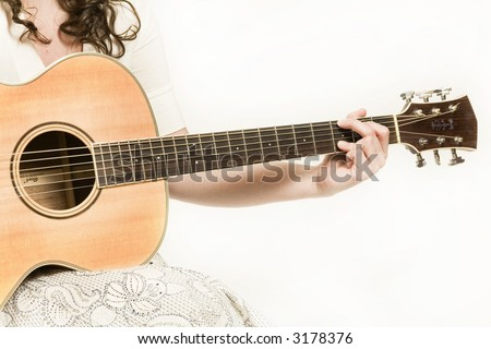 Young woman singing and playing an acoustic guitar - stock photo
