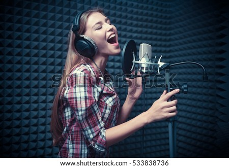 Young woman singing in a recording studio