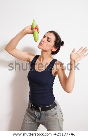 Young woman singing in zucchini microphone. Concept of vegetarian dieting, raw food ingredients, healthy and joyful living - stock photo
