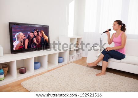 Young Woman Singing Karaoke With Microphone Looking At Television - stock photo