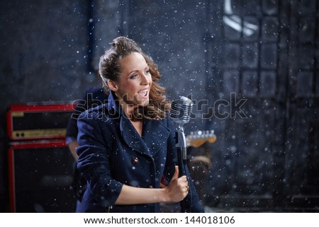 Young woman sings into microphone when shooting musical clip - stock photo