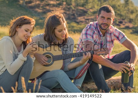 Young woman sings playing guitar with friends on sunset outdoor - stock photo