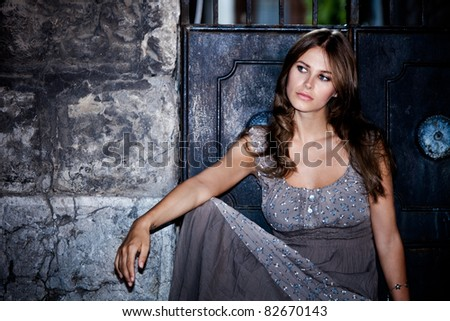 young woman sit in front of entrance gate on the street - stock photo