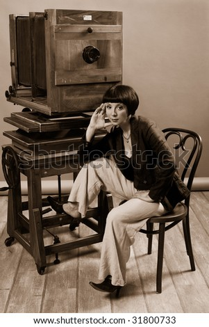 Young woman sit near the old vintage camera in photographic studio - stock photo