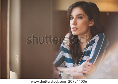 Young woman sitting alone at a cafe.