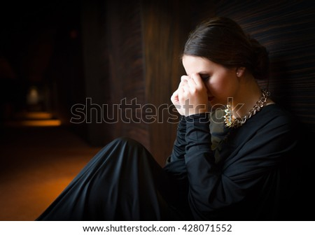 Young woman sitting alone on ground - stock photo