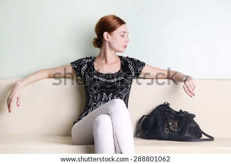 Young woman sitting and looking at her watch - stock photo