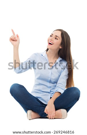 Young woman sitting and pointing up - stock photo