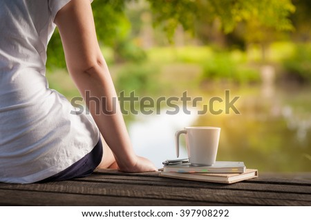 Young woman sitting and put down her hand beside coffee cup and notebooks on rustic wood bench with rural lake view in morning time on weekend