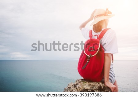 Young woman sitting and relaxing on a cliff near ocean (intentional sun glare)