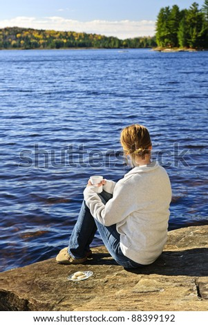 Young woman sitting and relaxing on lake shore in Algonquin Park, Canada