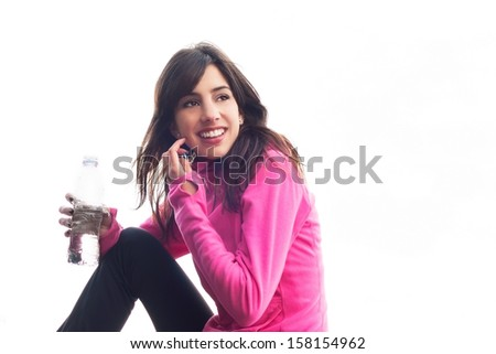 Young woman sitting and resting after exercising and holding a water bottle