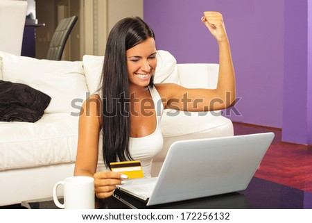 Young woman sitting  and  shopping online with credit card - stock photo