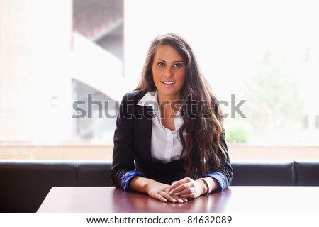 Young woman sitting at a table while looking at the camera - stock photo