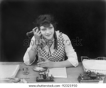 Young woman sitting at her desk in an office with a telephone in her hands - stock photo