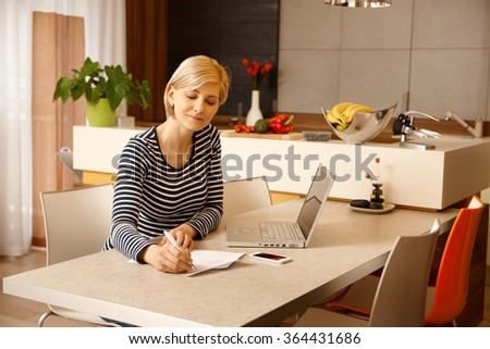 Young woman sitting at table at home, working.
