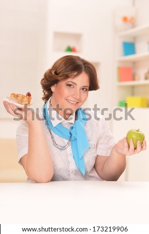 Young woman sitting at table with an apple and cake. Dieting concept - stock photo