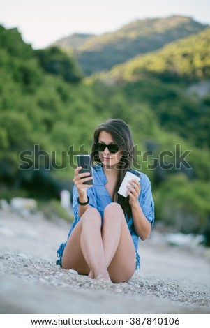 Young woman sitting at the beach drinking coffee and using her mobile phone - stock photo