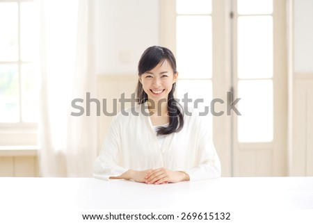 young woman sitting at the table - stock photo