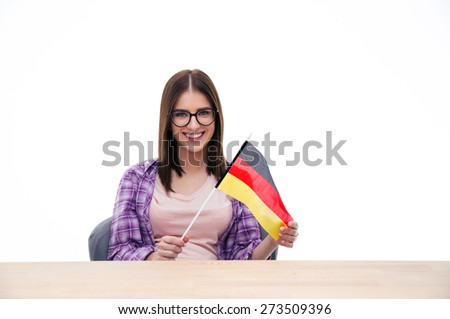 Young woman sitting at the table and holding German flag over white background. Looking at camera - stock photo