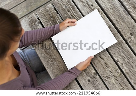 Young woman sitting at wooden table with a booklet with white cover. (see file 211954063 without slightly colored in the corners) - stock photo