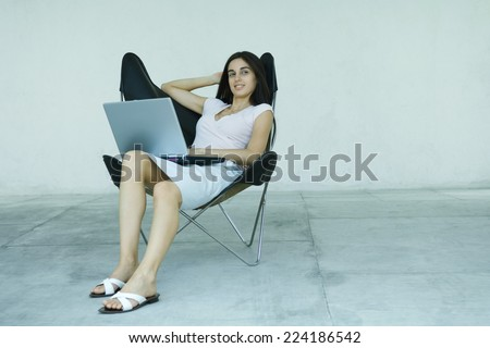 Young woman sitting back in chair, using laptop, full length portrait - stock photo